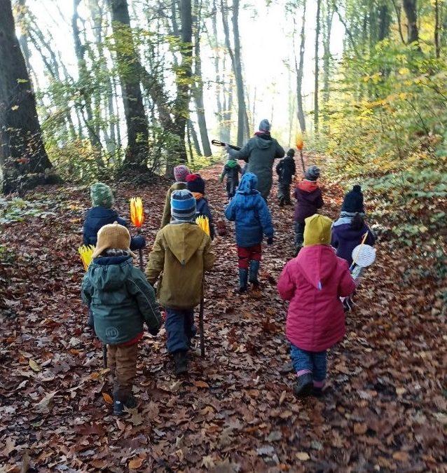 Kinder laufen mit Laternen durch den Wald